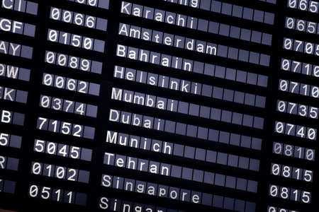 departure board: A flight schedule at the airport show Karachi, Amsterdam, Bahrain, Helsinki, Mumbai, Dubai, Munich, Tehran, Singapore