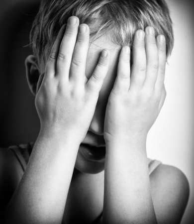 fear child: BW portrait of sad crying little boy covers his face with hands Stock Photo