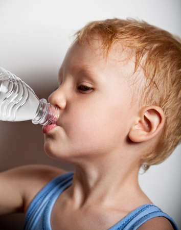 Quench thirst. The boy is drinking mineral water from plastic bottle photo