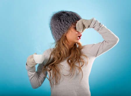 Diseased girl takes a hot effective medicine to cure flu. Sad face and runnynose.  Stock Photo
