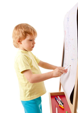 Four-year old boy drawing picture on easel. Isolated on white Imagens