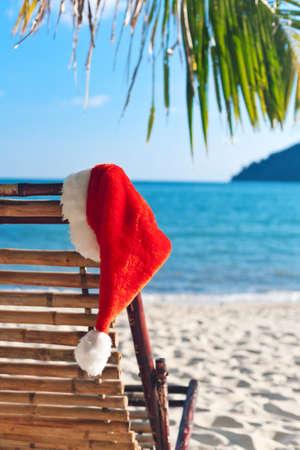 palm frond: Cappello di Babbo Natale rosso appeso sulla sedia di spiaggia sotto Palma. Natale nel concetto di clima tropicale