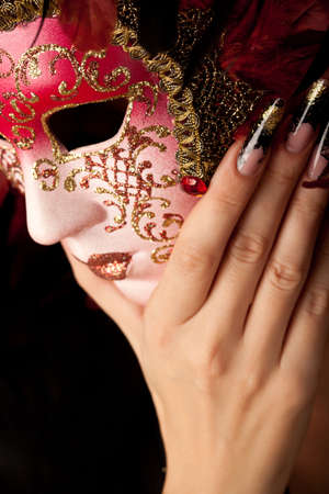 Under the mask. Human hand with beautiful manicure on long finger holding venetian mask photo