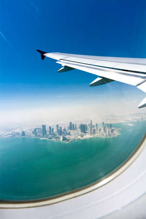 airplane window: Birds-eye view on the modern city under the wing of an airplane. Doha, Qatar