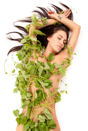 fille nue sexy: Portrait of young beautiful woman nude ? green herbe ? puce ? her ? white background wrapped leaves