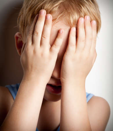 Portrait of sad crying little boy covers his face with hands Stock Photo - 8431010