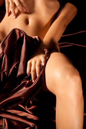 Young sexy nude woman covers her body with silk cloth Stock Photo