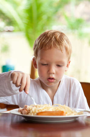 four year old: Four year old boy eating spaghetti with sausages outdoors