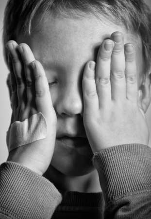 BW portrait of sad crying little boy covers his face with hands. One hand with medical plaster.