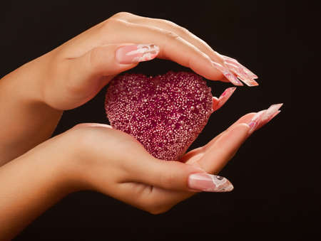 long day: Human hands with long acrylic fingernail and beautiful manicure holding pink heart. Over black Stock Photo