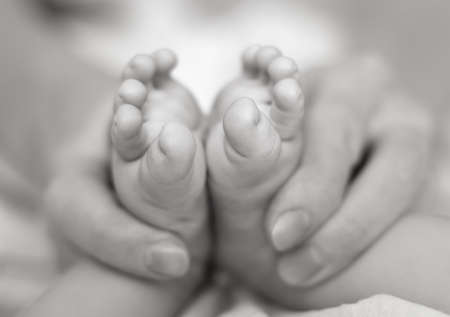 Mother gently hold baby legs in hand. Slightly toned black & white image with soft focus on babies foot