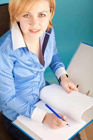 Businesswoman with pencil checks the documents in a folder photo