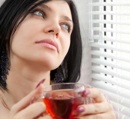 soledad: Niña morena reflexiva, beber té en la ventana con las ciegas