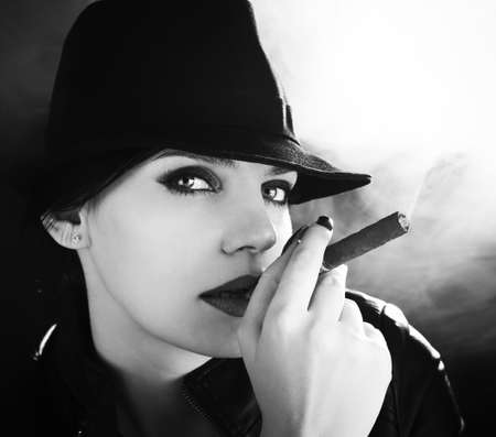 BW portrait of attractive brunette in a felt hat smoking a cuban cigar