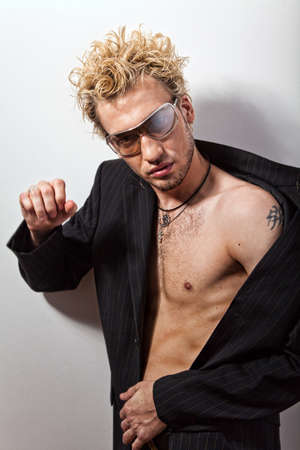 Portrait of handsome stylish blond man in sunglasses and a coat over her naked body. Image with moving right hand photo