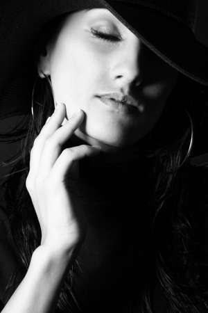 BW Portrait of attractive brunette girl in the hat close her eyes and gently touch your face photo