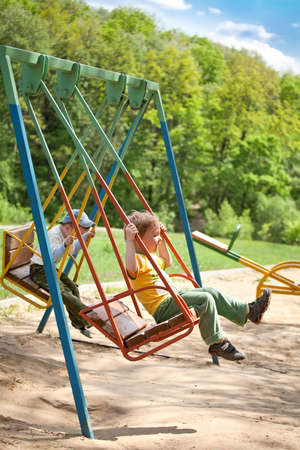 Two five year old boy swinging on a swing in the park on the playground photo