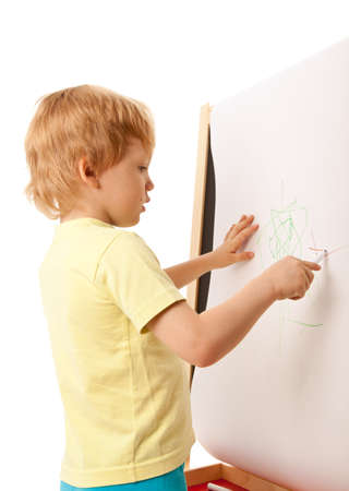 Four-year old boy drawing picture on easel. Isolated over white