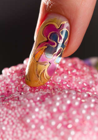 lacquered: Long acrylic fingernail with beautiful multilayer manicure touching beads. Shallow depth of field