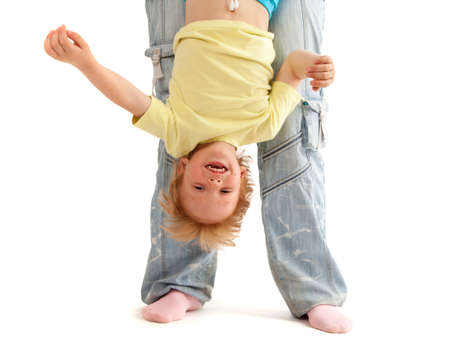 Mother hold her smiling son upside down. Isolated on white photo