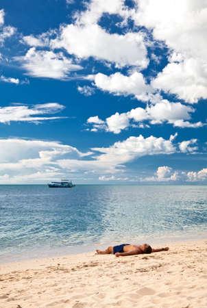 Man relax on sand under bright sun at lonely beach. Thailand. Island Koh Chang,  beach Kai Bae photo