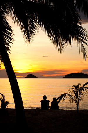 Silhouette of a romantic couple sitting on a beach under palm trees at sunset. Sunlight is shimmering off of the water. Other islands can be seen at the distance. photo