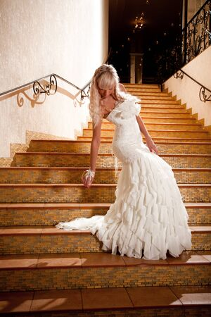 Beautiful girl in a wedding dress going down the stairs photo