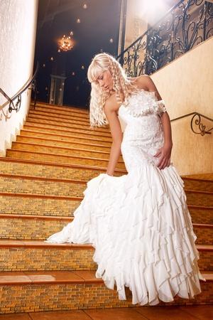 bajando escaleras: Hermosa niña rubia con un vestido de boda bajar las escaleras