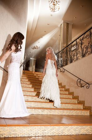 Two girls in a beautiful wedding dress on the stairs Stock Photo