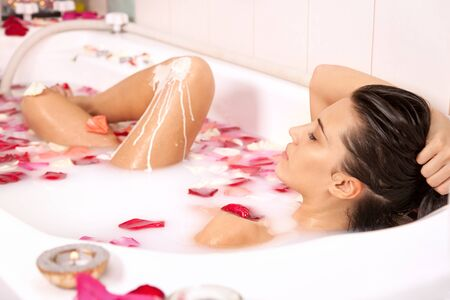 Attractive naked girl enjoys a bath with milk and rose petals. Spa treatments for skin rejuvenation