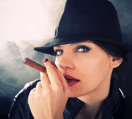 Morena atractivo en un sombrero de fieltro fumar un cigarro cubano Foto de archivo