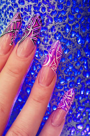 Human fingers with long acrylic fingernail and beautiful manicure in pink style over blue glass photo