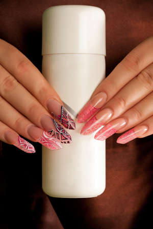 long nail: Human hands with long acrylic fingernail and beautiful manicure hold white plastic bottle with nail sculpting liquid. Over brown silk