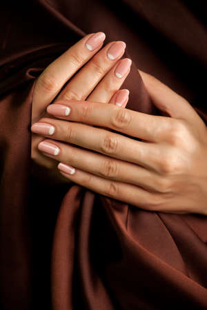 long nail: Groomed human hands with classic french-style manicure wrapped with brown silk