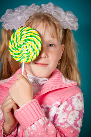 A young girl close one eye with lollipop. Over blue background Stock Photo - 10122129