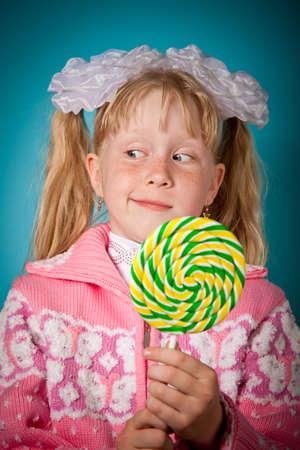 timidity: Crafty girl with big lollipop. Over blue background Stock Photo