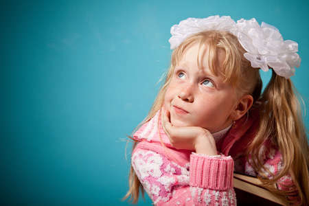 puzzlement: Portrait of confused girl holding two books. Girl slightly puzzlement. Isolated on blue background