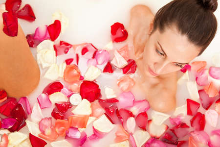 Attractive naked girl enjoys a bath with milk and rose petals. Spa treatments for skin rejuvenation Stock Photo - 10299268