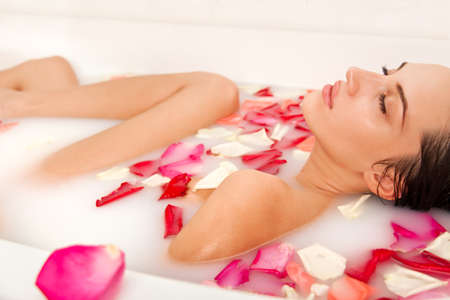 body milk: Attractive naked girl enjoys a bath with milk and rose petals. Spa treatments for skin rejuvenation