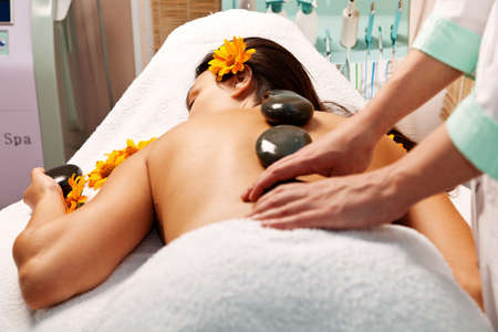 Stone therapy. Woman getting a hot stone massage in spa salon Stock Photo - 10425329