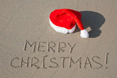 Merry Christmas written on the sand beach under red Santa hat photo