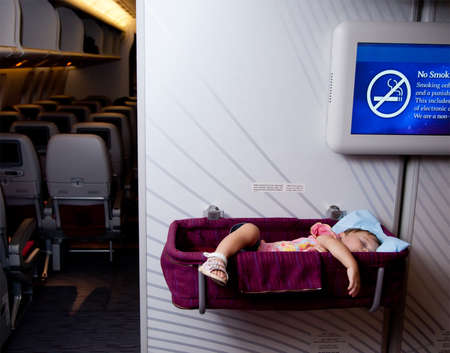 Travel with children. Small two year old baby girl sleep in a special bassinet on a airplane Banque d'images