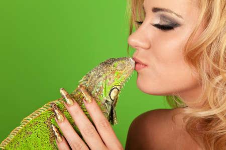 unas largas: Retrato de una mujer joven con la manicura bonita besando a una iguana