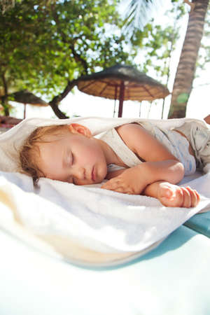 Little baby girl asleep on a chaise lounge outdoors in the shade of palm trees photo