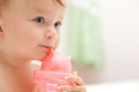 The little blue-eyed baby girl drinks juice from a bottle photo