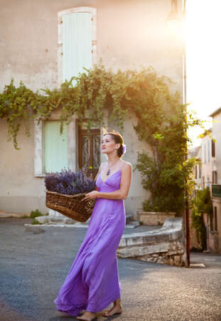 france perfume: Provence, France  Tiny town of Sault  Girl with a basket of freshly cut lavender in the old city Today the tiny town of Sault is lavender capital of Provence  Every year in august in the town start Lavender Festival  Stock Photo