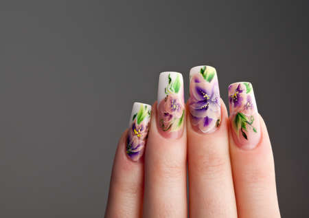 Human fingers with beautiful spring manicure over gray background