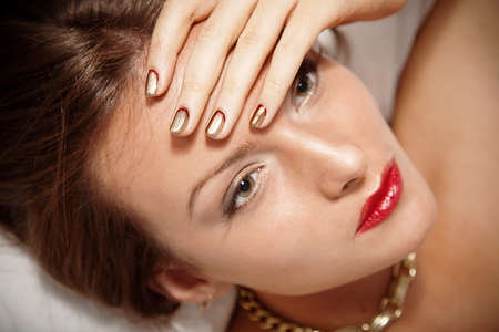 Portrait of attractive girl with beautiful metallic spiral pattern Minx nails photo