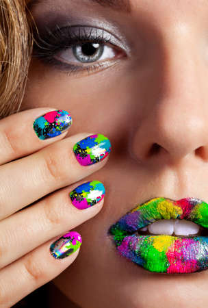 Half face of attractive girl with beautiful multicolor holographic Minx nails and bright colorful make-up Stock Photo