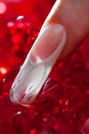 Finger with long acrylic fingernail and beautiful manicure touch a red crystals photo